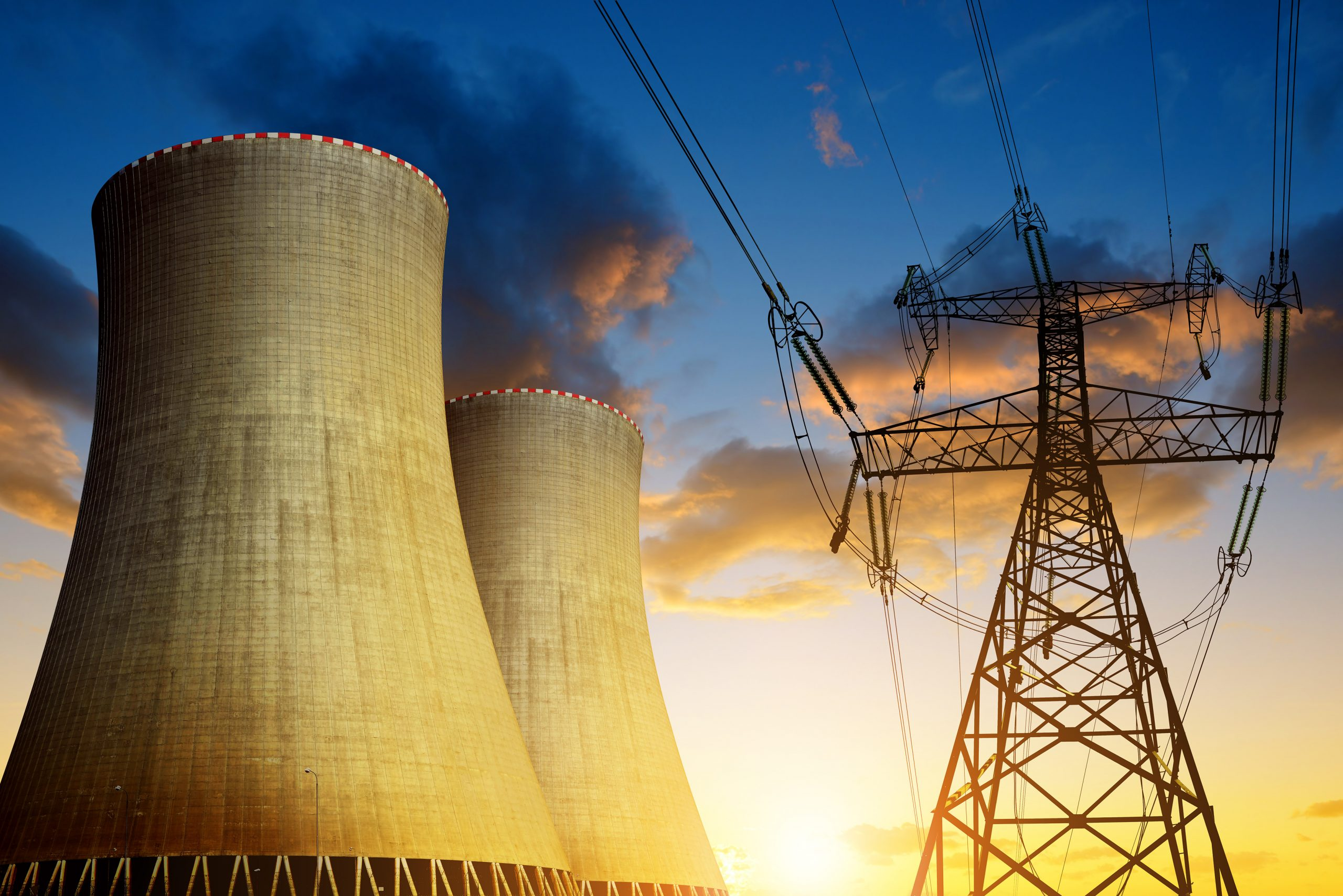 Image shows cooling towers of a nuclear plant next to high voltage transmission and distribution tower and lines.